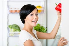 Woman takes red pepper from opened fridge. Woman takes red pepper from the opened fridge full of vegetables and fruit. Concept of healthy and dieting food royalty free stock images