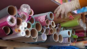 Woman takes roll of decorative paper from wooden rack