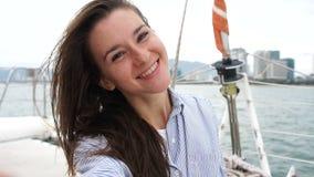 Woman takes self portrait photo while enjoying vacation on a yacht. Young woman takes self portrait photo while enjoying vacation on a yacht stock footage