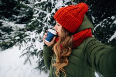 Woman takes selfie with coffee in winter snowy cold day stock photography