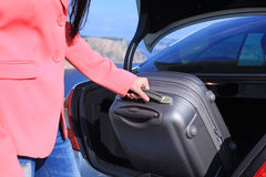 Woman takes suitcase from the car trunk. Arrived on vacation at a resort Royalty Free Stock Photography