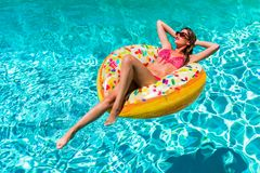 Woman takes a sunbath in a donut shaped pool float on a hot summer day. Beautiful, young woman takes a sunbath in a donut shaped pool float on a hot summer day royalty free stock photography