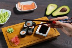 Woman takes the sushi rolls using chopsticks. royalty free stock images