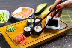 Woman takes the sushi rolls using chopsticks. Stock Images