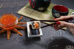 Woman takes the sushi rolls using chopsticks. Stock Photography