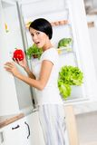 Woman takes sweet pepper from opened fridge Royalty Free Stock Image