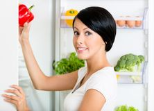 Woman takes sweet pepper from opened refrigerator Stock Images
