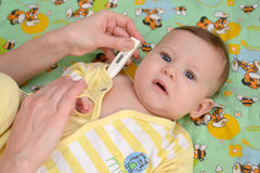 The woman takes temperature to the sick baby the electronic ther. Mometer Royalty Free Stock Image