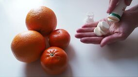 Woman takes Vitamin C to hand with background of oranges on table Above Close up