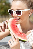 Woman takes watermelon. Concept of healthy and dieting food. Woman biting watermelon from the opened fridge full of vegetables and fruit. Concept of healthy and Royalty Free Stock Photography