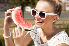 Woman takes watermelon. Concept of healthy and dieting food. Young smiling woman takes watermelon from the opened fridge full of vegetables and fruit. Concept of Stock Images