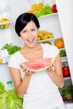 Woman takes watermelon from opened fridge Stockbilder