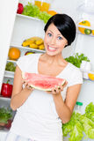 Woman takes watermelon from opened refrigerator Stock Photography