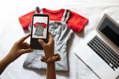 Free Woman Taking A Photo Of An Article Of Clothing To Sell Online. Concept Of Selling Clothes Online. Royalty Free Stock Images - 185326309