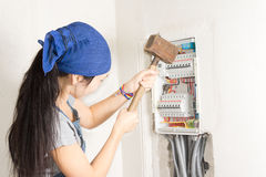 Woman taking aim at an electrical fuse box. With a large wooden mallet in an effort to solve her supply problems royalty free stock image
