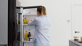 Woman taking apple from fridge at home kitchen stock footage