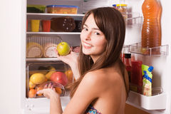 Woman taking apple out of fridge. Young woman taking apple out of fridge royalty free stock photos