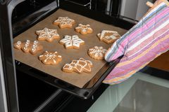 Woman taking baking tray with tasty Christmas cookies Royalty Free Stock Photo