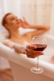 Woman taking a bath. Beautiful young woman enjoying pleasant bath with foam, holding a glass of wine, focused on hand with glass Stock Photo