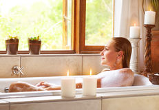 Woman taking bath. Picture of beautiful woman taking bath at home, cute female lying down in bathtub, warm candle light, romantic atmosphere, pampering and stock image