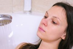 Woman is taking a bath. She pours her body water from the shower. Close-up face. royalty free stock photo