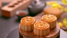 Woman taking beautiful moon cake pastry to eat and share with family to celebrate Mid-Autumn Festival. Reunion event concept
