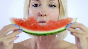 Woman taking bite from fresh watermelon slice. Various shots of woman eating slice of fresh watermelon on white background stock video footage