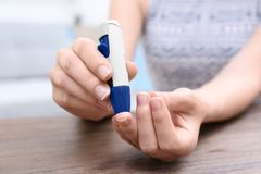 Woman taking blood sample with lancet pen. Indoors Royalty Free Stock Photo