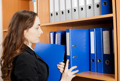 Woman taking a blue folder from shelf Stock Image