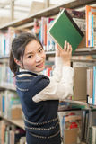 Woman taking a book from a bookshelf Stock Photos