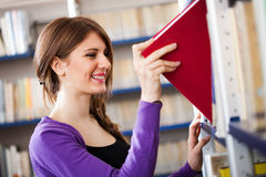 Woman taking a book in a library Royalty Free Stock Photo