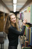 Woman taking a book in old library Royalty Free Stock Images