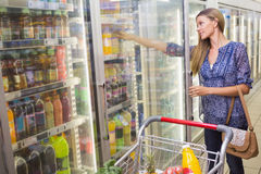 A woman taking a bottle in the frozen aisle Royalty Free Stock Photo