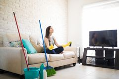 Woman taking a break from cleaning home. Woman meditating, sitting on sofa while cleaning home in the living-room Royalty Free Stock Images