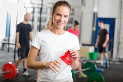 Woman taking a break at crossfit center. Smiling and fit woman rests after workout at a crossfit fitness center. People, jump boxes and weights in the background Stock Photography
