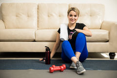 Woman taking break from exercising at home Stock Images