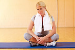 Woman taking break in gym Stock Images