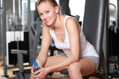 Woman taking a break at the gym. Young woman in health club Stock Image