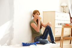 Woman taking a break from home renovation. Portrait of mature caucasian woman sitting on floor and having  tea, taking a break from home renovation work Stock Photo