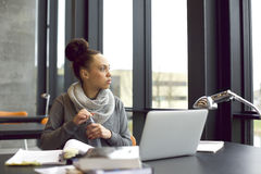 Woman taking a break while studying in library. Young african american woman holding water bottle and looking away while studying in library. Female student Royalty Free Stock Image