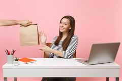 Woman taking brown clear empty blank craft paper bag, work at office with pc laptop isolated on pink background. Food. Products delivery courier service from royalty free stock photography
