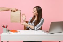 Woman taking brown clear empty blank craft paper bag, work at office with pc laptop isolated on pink background. Food. Products delivery courier service from royalty free stock photos