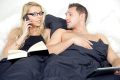 Woman taking a call in bed Royalty Free Stock Image