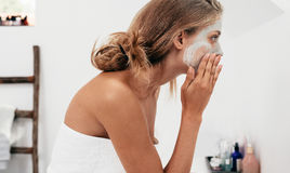 Woman taking care of her facial skin. Side view shot of young woman applying facial cosmetic mask in bathroom.  Female taking care of her face skin Royalty Free Stock Photos