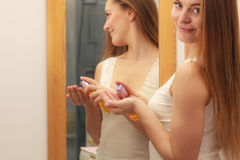 Woman taking care of her long hair applying cosmetic oil Stock Photo