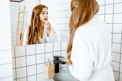 Woman taking care of herself in the bathroom. Portrait of a beautiful young women applying cosmetics on her face while looking at the mirror in the bathroom royalty free stock image