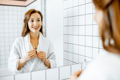 Woman taking care of herself in the bathroom. Portrait of a beautiful young women applying cosmetics on her face while looking at the mirror in the bathroom stock photography