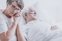 Woman taking care of husband. Sad elderly women taking care of her dying husband with alzheimer`s stock images