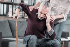 Woman taking care of senior husband with strong headache. At home stock photography