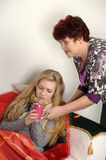 Woman taking care of a sick daughter. Woman taking care of a sick teenage daughter Royalty Free Stock Photo